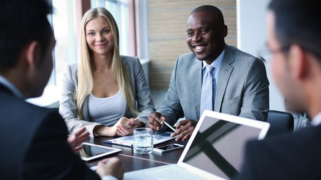 business interview: Happy colleagues having friendly talk at meeting Stock Photo