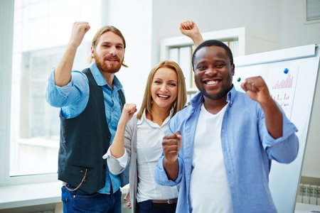 Cheerful business team expressing joy or victory