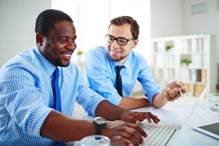 puesto de trabajo: Dos hombres de negocios jovenes que discuten los datos para nuevo proyecto