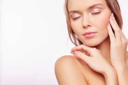 and shoulders: Mujer contenta joven con maquillaje natural tocar su cara