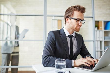 Jonge zakenman in formalwear typen op laptop
