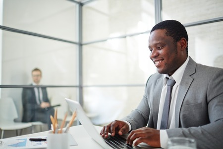 african business man: African businessman in formalwear typing on laptop