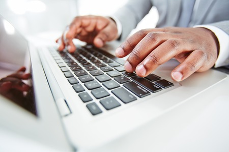 Hands of African businessman typing