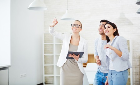 Pretty realtor showing new flat to young couple