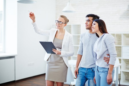 Pretty realtor consulting young couple about buying flat