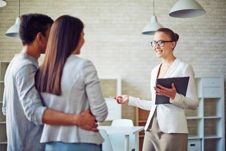 agente comercial: Mujer consultor�a corredor joven pareja en la oficina de bienes ra�ces