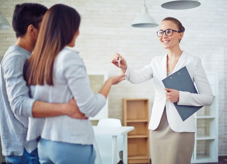 key: Female broker giving young couple key from new flat