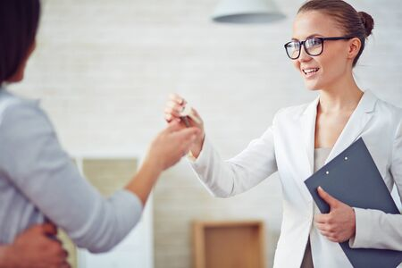 broker: Young female broker giving her client key from new flat Stock Photo