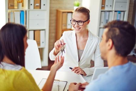 Weibliche Immobilienmakler geben junge Paar Schlüssel von Immobilien