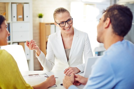 계약의 젊은 부부 계약 조건을 설명하는 여성 부동산 중개인 스톡 콘텐츠