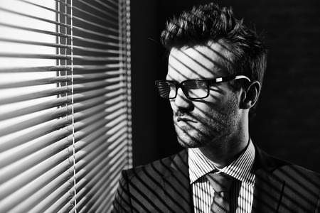 jalousie: Serious young businessman in eyeglasses looking through jalousie