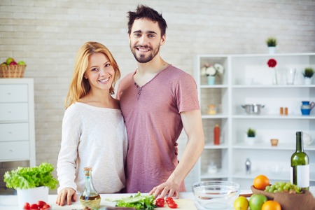 vegetables young couple: Happy young couple standing by table with vegetarian food in the kitchen
