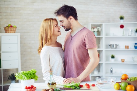 vegetables young couple: Happy young couple of vegetarians flirting in the kitchen Stock Photo