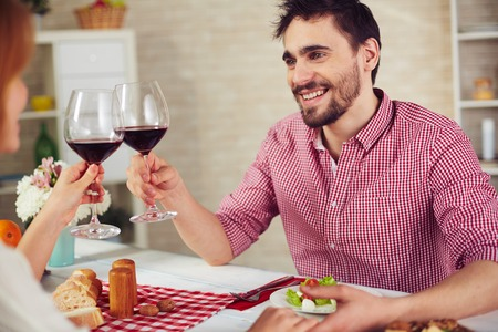 Happy young man with glass of red wine toasting with his wife