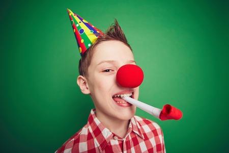nariz roja: Chico divertido con la nariz roja que se divierten en la fiesta de cumplea�os Foto de archivo