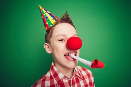 Funny kid with red nose having fun on birthday party
