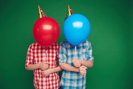 birthday celebration: Two boys hiding behind red and blue balloons