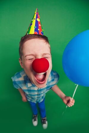 Goofy boy with balloon and clown nose shouting at fool�s day celebration photo