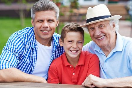 senior group: Happy senior man, young man and boy looking at camera Stock Photo