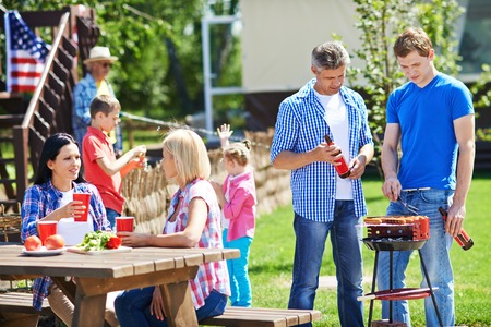 adult family: Two men frying sausages on grill outdoors with young women talking by table near by