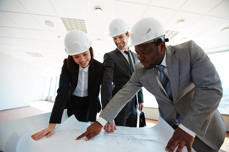 protective helmets: Confident architects in protective helmets looking at blueprint Stock Photo
