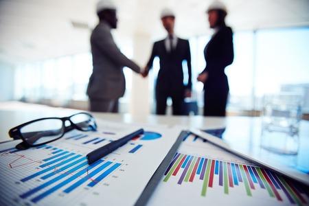 reuniones empresariales: Los documentos comerciales en el fondo de los tres socios de negocios