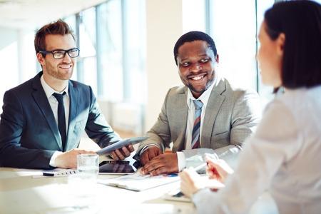 Lachend zakenlieden luisteren naar jonge vrouwelijke tijdens interview