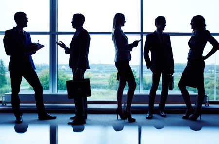 Several business partners communicating against window photo