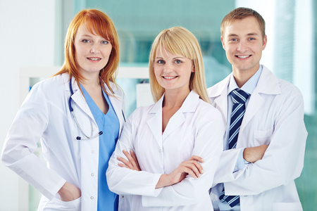 white coats: Happy young colleagues in white coats looking at camera Stock Photo