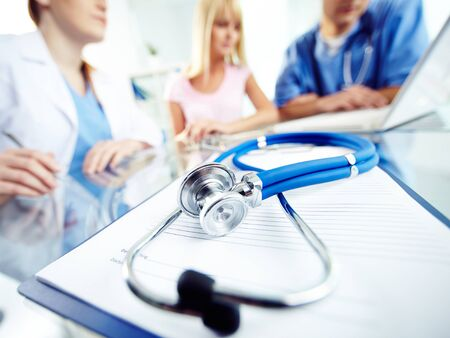 practitioners: Prescription form and stethoscope on background of working practitioners Stock Photo