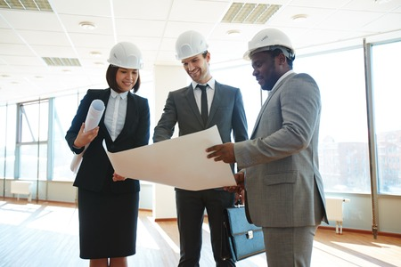 protective helmets: Confident architects in protective helmets discussing blueprint in office Stock Photo