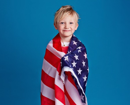 wrapped up: Little patriot wrapped up in USA flag Stock Photo