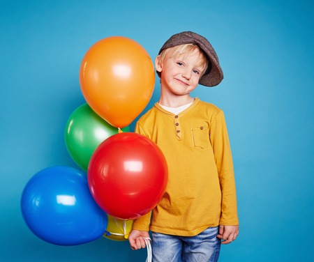 celebration party: Cute lad with multi-color balloons looking at camera