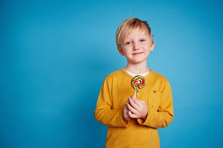 lad: Cute lad with sweet lollipop looking at camera Stock Photo