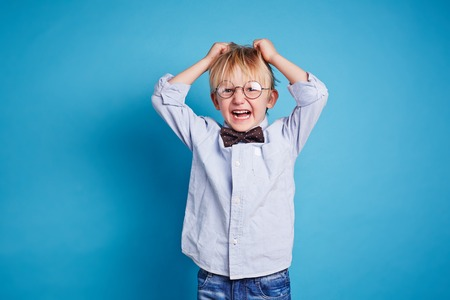 dissatisfaction: Little boy in smart casual expressing dissatisfaction
