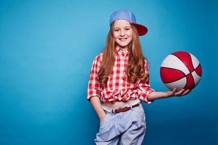 sport balls: Cute girl with basketball looking at camera