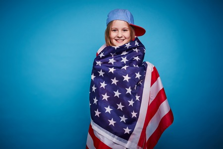 wrapped up: Cute girl wrapped up in USA flag looking at camera Stock Photo