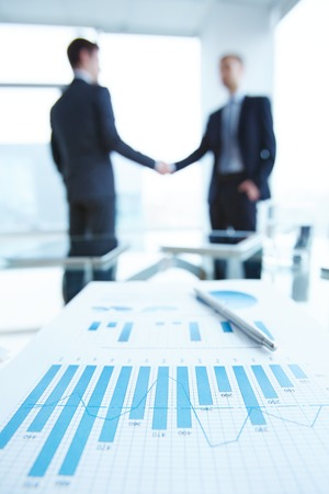business deal: Business document with chart and graph on workplace with two men handshaking on background