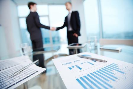 stretta mano: Documenti aziendali con dati economici e penne sul posto di lavoro su sfondo di due partner handshake