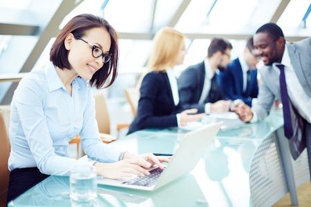 mujeres felices: Tipificaci�n Empleado bonito en la computadora port�til en el entorno de trabajo