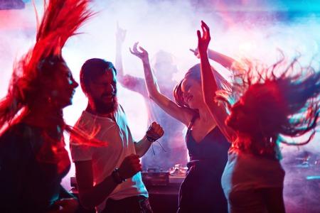 fiesta: Grupo de amigos energéticos que bailan en club nocturno