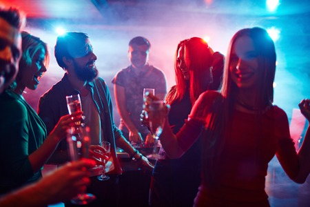 party night: Happy friends toasting at night party Stock Photo