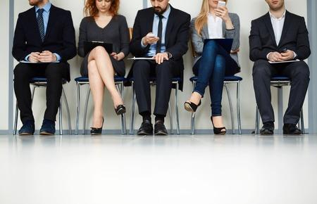 personas sentadas: Línea de los jóvenes que se sientan por la pared a la espera de su turno para la entrevista