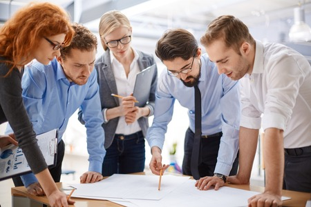group of business people: Team of employees studying blueprints at meeting