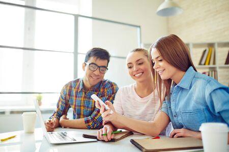 Grupo de adolescentes felices navegando en el smartphone