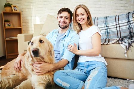 familias felices: Joven pareja feliz y su mascota disfruta resto a casa el fin de semana Foto de archivo