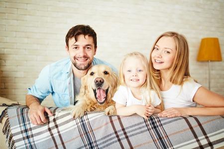 Feliz pareja joven con su hija y perro mirando a la cámara