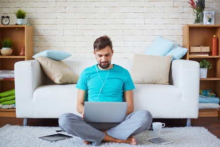 barefoot man: Handsome guy with earphones using laptop at home Stock Photo