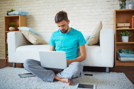 Young man listening to music in earphones while networking on laptop at leisure Stock Photo