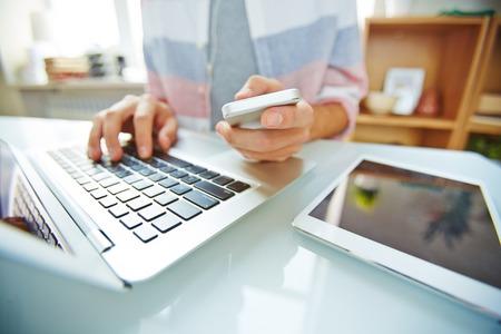 Handen van jonge man met smartphone en typen op de laptop